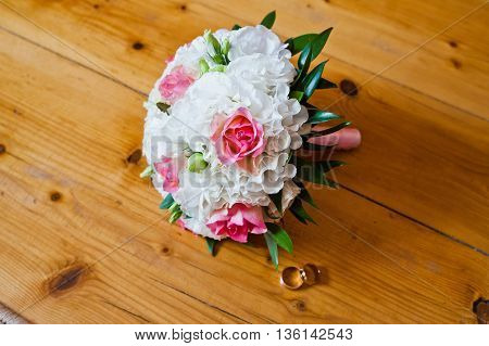 Wedding Bouquet With Rings At Wooden Background