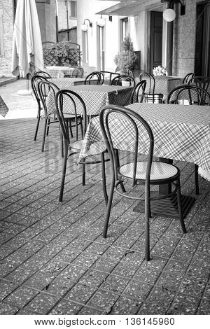 SAN PELLEGRINO TERME, ITALY - JUNE 20, 2016: outdoor area of a pub in San Pellegrino Terme, at the start of the summer season; empty tables waiting for the first customers of the season.