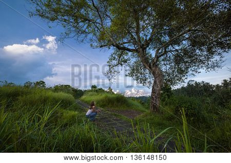 Young lady sitting under big tropical tree and looking on it