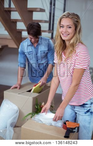 Portrait of woman unpacking bowls from box with man at home