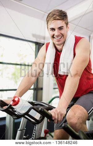 Portrait of man working out on exercise bike at spinning class in gym