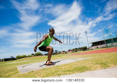 Male athlete preparing to throw shot put ball in stadium