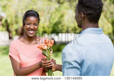 Happy woman having flowers at park
