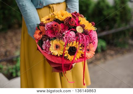 girl holding colorful bouquet with different Gerbera flower composition
