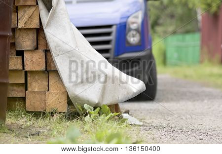 A stack of the joists covered with material in focus and a truck in the blurred background, outdoor shot with selective focus
