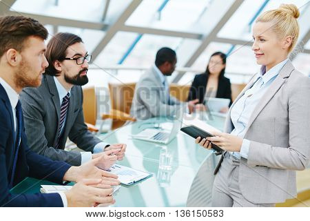 Female leader talking to male employees at meeting