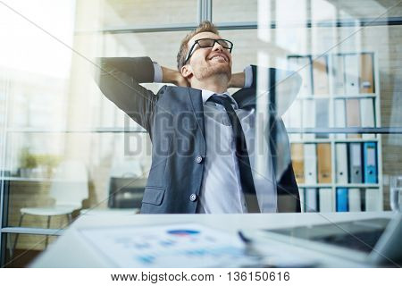 Happy businessman sitting with hands behind head
