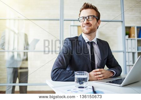 Handsome businessman sitting in office and smiling