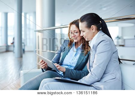 Two businesswomen watching something on touchpad