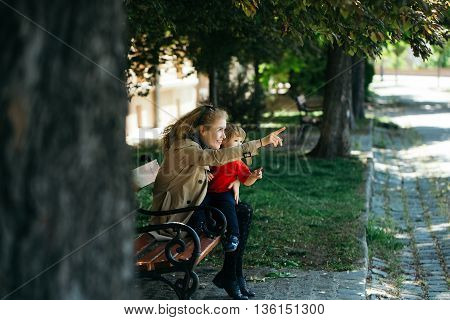 Little boy shows the girl something. Pretty girl babysits adorable boy in the park
