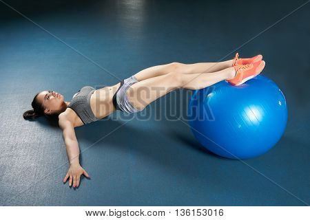 Beautiful body builder makes exercise with large blue ball on the floor of the gym