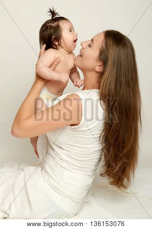 Mom lifts baby and kisses, play and having fun