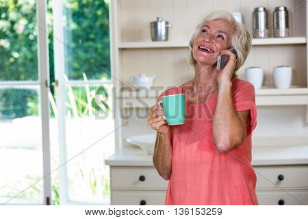 Senior woman talking on phone while having coffee in kitchen at home