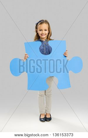 Beautiful little girl holding a big blue Puzzle