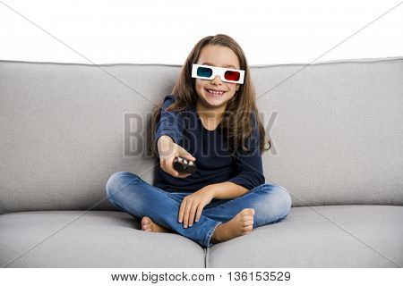 Little girl holding a TV remote control and wearing 3d glasses