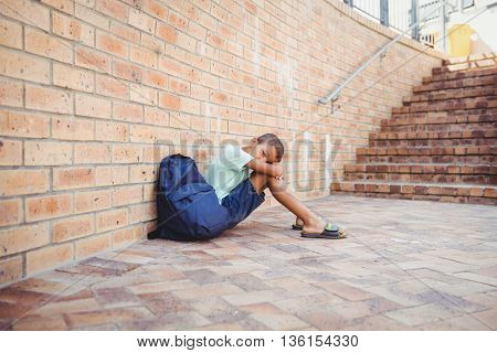Sad boy with his head on his knees sitting in front of school