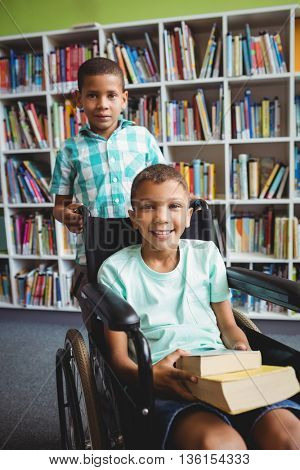 Little boys holding books in the library