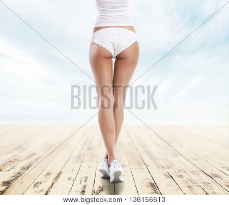 Closeup of sexy and sporty female body. Girl with a perfect body shape resting on a summer vocation. Sea, sky and beach background.