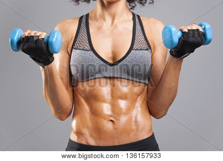 Fit woman lifting weights on grey background