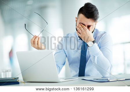 Businessman rubbing eyes at laptop