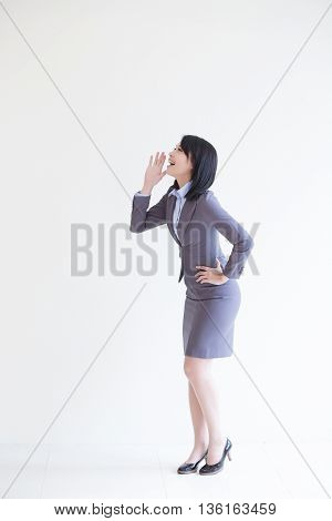 business woman stand and shout to copy space with white wall background great for your design or text asian