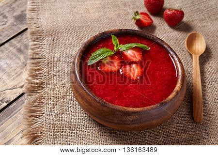 Healthy organic fresh strawberry cream soup vegetarian cold sweet berry smoothie summer food on rustic wooden background table