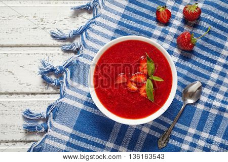 Fresh organic strawberry cream soup vegetarian cold sweet berry smoothie summer food on white wooden background table