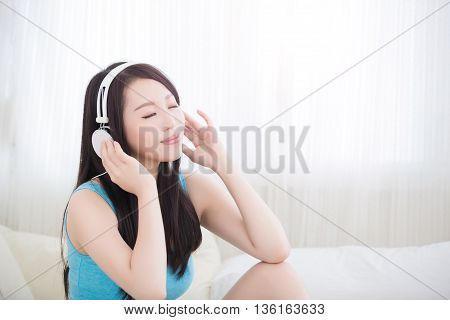 Young woman closed eye and enjoying the music and relax sit at home asian beauty
