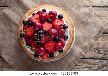 Fresh raw strawberry cake homemade traditional summer gourmet sweet dessert bakery food decorated with berries and whipped cream on rustic background table