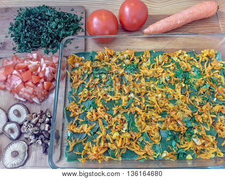 Nettles green lasagna cooking with mushrooms tomatoes and carrot, food from weed, using wild plants