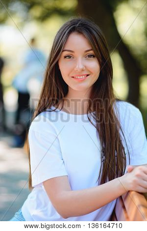 Portrait Of A Woman Sitting On Bench In Park
