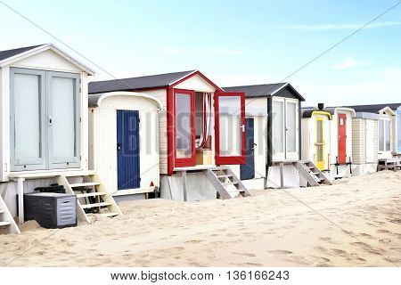 Beach huts or houses and blue sky. Multicolored beach bathing huts with white sand and clear blue sky. Beach scene with copy space.
