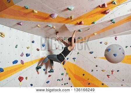 Portrait of slim dexterous Asian woman climbing indoors
