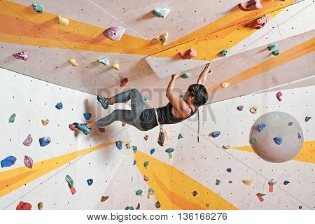 Pretty young female athlete climbing in gym