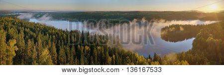 Lake view landscape at Aulanko nature park in Finland. Peaceful panorama image with a foggy lake and the Sun rising above the forest one late summer morning.