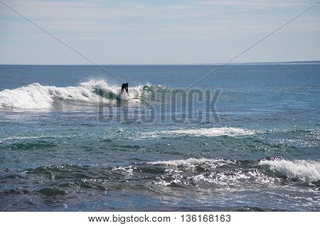 KALBARRI,WA,AUSTRALIA-APRIL 23,2016: Tourist surfing in the glistening Indian Ocean waves on a clear day at Blue Holes Beach in Kalbarri, Western Australia.