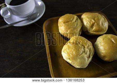 Bread rolls and a black coffee in a dish.