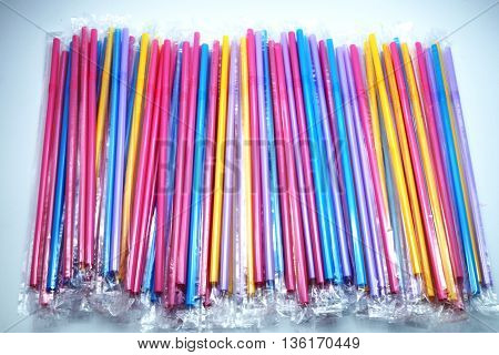 Colorful plastic drinking straws in plastic wraps on blue-white background. Focus on extended straws. Space for texts.