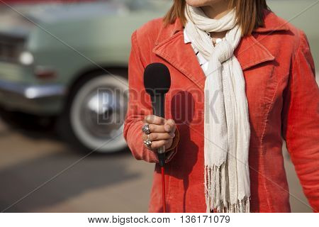 Female journalist holding microphone conducting media interview