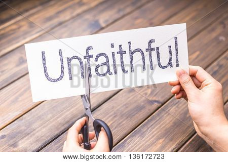woman cuts white paper with word unfaithful on table