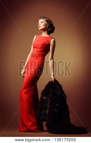 Full length portrait of a beautiful woman in red dress and luxurious fur coat. Luxury, rich lifestyle. Fashion shot.