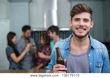 Portrait of smiling young man holding beer bottle while friends enjoying in background
