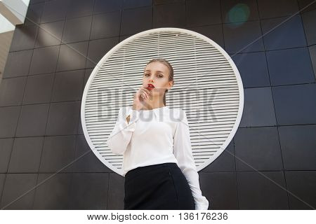 Beautiful blonde businesswoman with red lips against of building wall