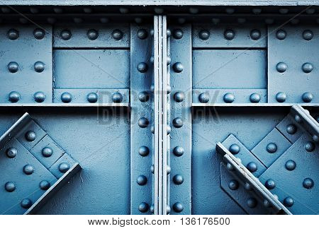 background or texture detail blue silver riveted girder railway bridge