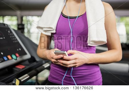Mid section of woman listening to music on treadmill at gym