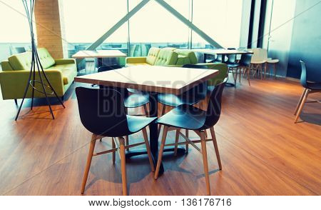 design, public place, furniture and interior concept - close up of restaurant interior with table and chairs