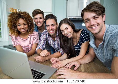 Portrait of multi-ethnic friends smiling while using laptop on table at home