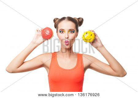 Portrait of brunette with make-up holding two delicious bright donuts.White background.Isolated.