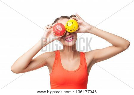 Portrait of cheerful young brunette covering eyes with bright donuts.Studio shot