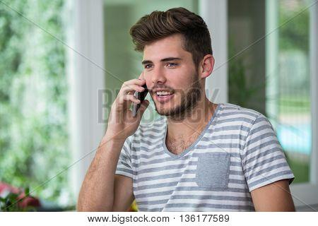 Smiling man talking on phone at home